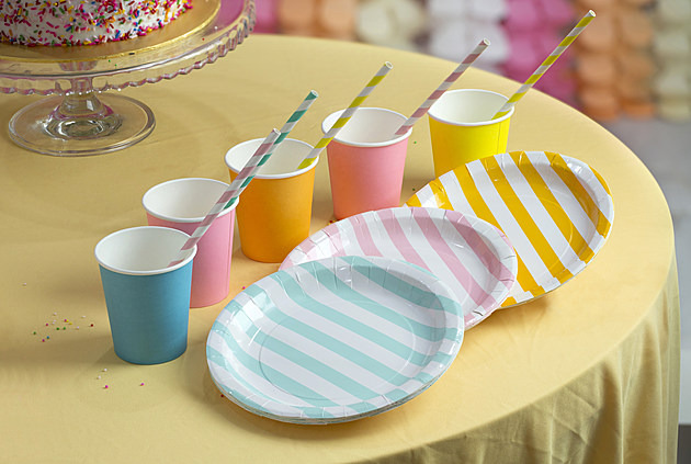 Colourful party paper cups and plates on table top.